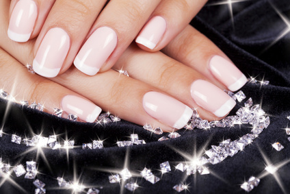 Beautiful woman's nails with french manicure and diamonds.